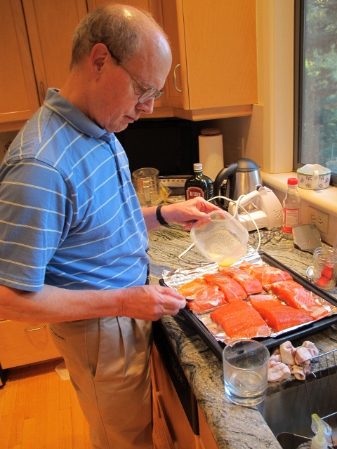 Jon pouring butter on salmon on kitchen counter. Photo by Barbara Falconer Newhall