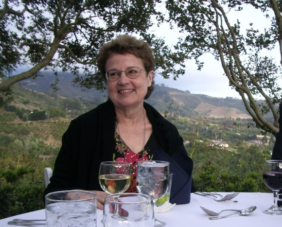 A 67-year-old woman enjoys herself at a white table cloth dinner with wine and a rural setting. BF Newhall photo