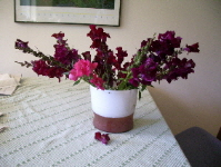 maroon snapdragons arranged awkwardly in a white glass vase. photo by bf newhall