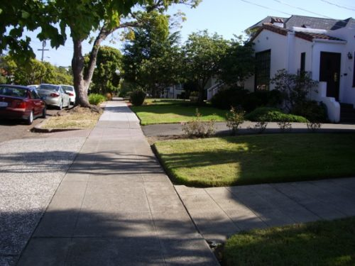 Wide sidewalk with houses visible from the street. Photo by BF Newhall