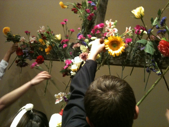 Children place flowers on a wooden cross. St. John's Episcopal Church, Oakland, CA. Photo by Barbara Falconer Newhall