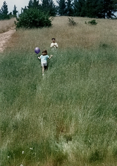 Peter and Christina playing in a field with a balloon.