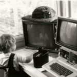 1986 home office with computer monitors, toddler and sleeping cat. Photo by BF Newhall.