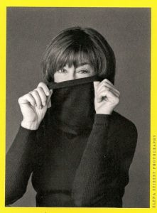 Nora Ephron holds her turtleneck shirt to cover her neck. Photo by Elena Seibert