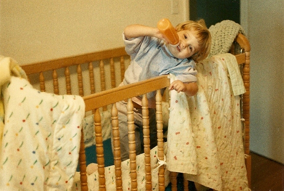 Two-year-old girl enjoys her bottle in her crib with blankies. Photo by BF Newhall