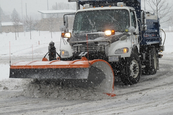 Snowplow clearing snow in a snowstorm at Eden Prairie, MN, Community Center. Photo 2013 by BF Newhall