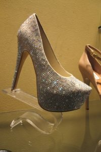Deevaa shoes in 2013 display case at Steve Madden store, with very high heels and thick sole and gold glitter. Photo by BF Newhall