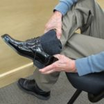 The father of the groom tries on patent leather formal shoes for the wedding at Men's Wearhouse. Photo by BF Newhall