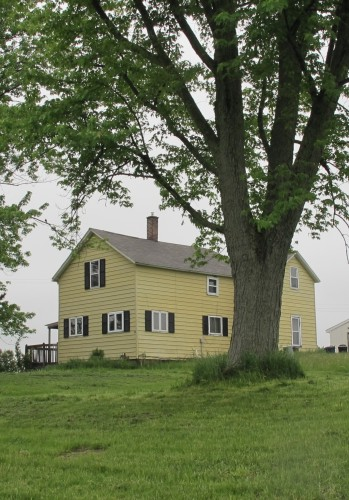 A two-story yellow frame farmhouse outside Scottville MI that is more than 100 years old. It once belonged to the David Falconer family. Photo by BF Newhall