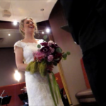 A bride in white lace gown with bouquet of mixed purple flowers laughs during her weddng ceremony. Photo by BF Newhall