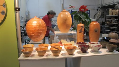 Potter Bob Pool at work in his studio with orange vases and bowls in the foreground. Photo by BF Newhall