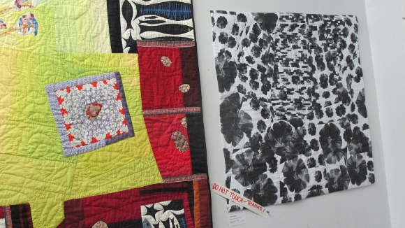 A colorful assymetrical art quilt and a quilt with black fleurs du mal against a white background by Donna Duguay of Berkeley, CA. Photo by BF Newhall