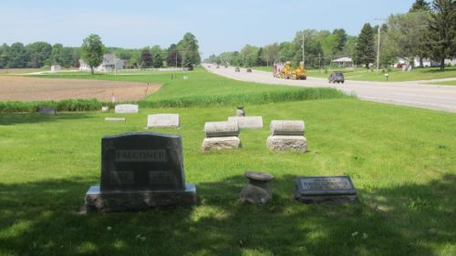 Brookside Cemetery in Amber Township, west of Scottville, MI. Headstones in foreground, farmland and busy Highway 10 in background. Photo by BF Newhall