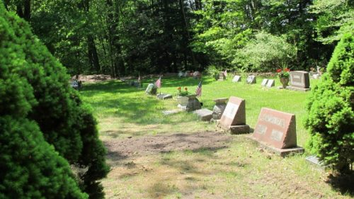 A row of grave markers and a newly covered grave at the Brookside Cemetery, Scottville, MI. Photo by BF Newhall