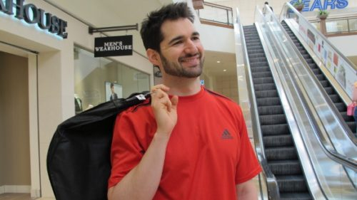 A relaxed groom in red t-shirt smiles and carries his Mens's Wearhouse tux in a bag. Photo by BF Newhall