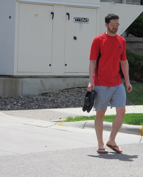A bridegroom wearing shorts and T-shirt on the day before his wedding carries his patent leather wedding shoes. Photo by BF Newhall