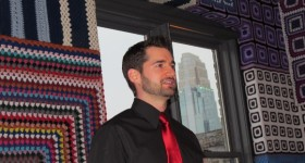 Young man wearing a black shirt and red tie greets guests at Minneapolis' Bachelor Farmer restaurant.