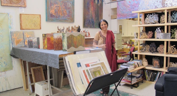 Painter Salma Arastu surrounded by paintings in her Berkeley CA studio. She wears a beige and red sari. Photo by BF Newhall