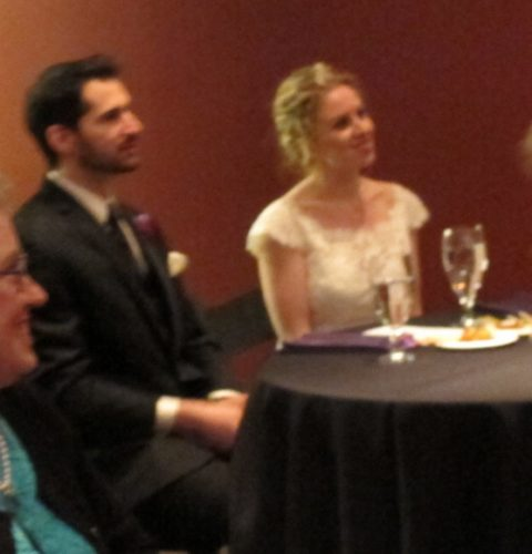 Brideand groom seated at a table with black tablecloths being toasted and smiling. Photo by BF Newhall