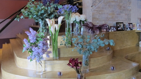 Several vases of flowers including callas, lilacs, and eucalyptus leaves decorate a stairway at the Five Event Center. Photo by BF Newhall