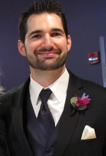 Handsome groom in tux, vest and tie with pink boutonniere before his wedding. Photo by BF Newhall