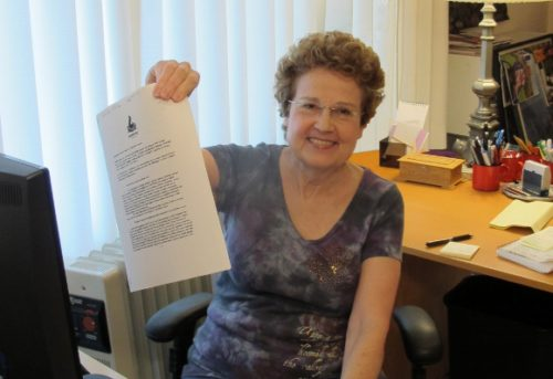 Writer Barbara Falconer Newhall in her writing room holding a copy of her book contract with Bondfire Books. Photo by Jon Newhall