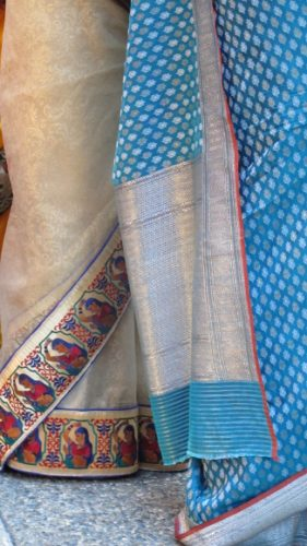 An ivory silk sari bordered with red and blue images with a blue dotted sari at an Indian wedding. Photo by BF Newhall