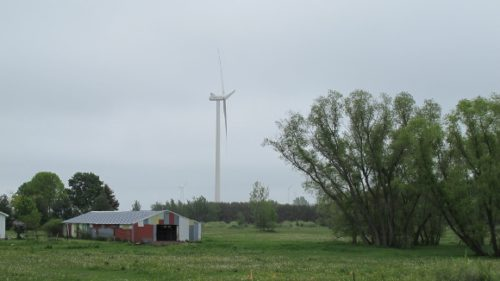 A wind turbine in the Lake Winds Energy Project towers above a painted shed in Mason County, Michigan. Photo by BF Newhall
