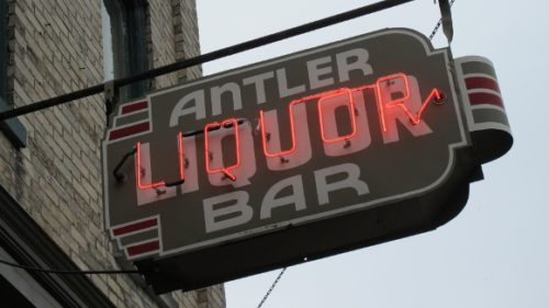 neon sign outside the antler bar in pentwater michigan with the word liquor in red. Photo by BF Newhall