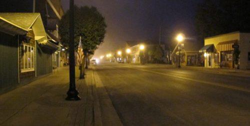 Street scene of Pentwater, Michigan, after dark, with North Hancock lit by street lights. Photo by BF Newhalls. pho