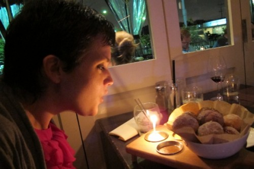 Pretty young woman blows out a birthday candle with her donut dessert at Waterloo & City in Culver City. Photo by BF Newhall