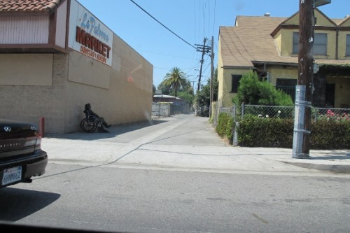 a man in a wheelchair sits in the shade of two-story building in a paved alley in los angeles. photo by bf newhall