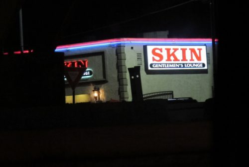 "a sign in los angeles advertising ""Skin, A Gentleman's Lounge."" Photo by BF Newhall"