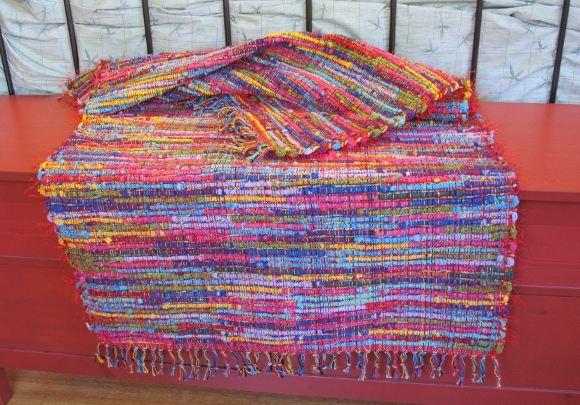 A multi-colored, mostly red hand-woven rug with fringe by Mary Helen Blohm. Photo by BF Newhall