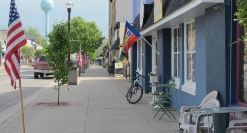 North Hancock Street, Pentwater, Michigan, with shops, flags and trees. Photo by BF Newhall