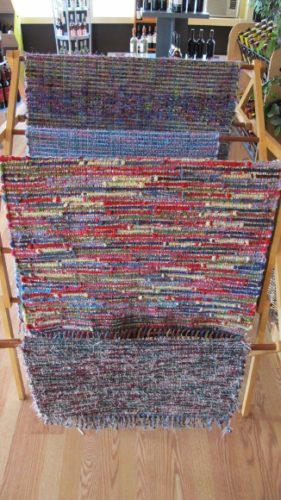 A rack in Gull Landing store showing several multicolored rugs hand woven by Mary Helen Blohm. Photo by BF Newhall