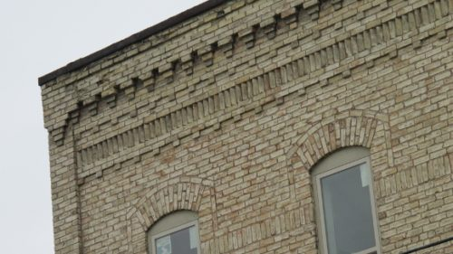 Detail of the gustafson building, pentwater, michigan showing the intricate yellow brick work and the tall narrow 19th century windows. Photo by bf newhall
