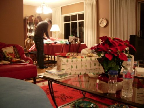 A man wraps his Christmas gifts in a living room cluttered ith decorations and gifts. Photo by BF Newhall