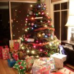 A christmas tree with lights, decorations and gifts piled up below. Photo by BF Newhall
