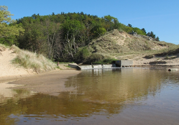 a tree covered dune along lake michigan with a channel and its dam at its base. Photo by BF Nehall