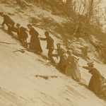 Turn of the 2oth century men and women on vacation struggling to climb the steep sandy slope of Eagle Top on Lake Michigan.