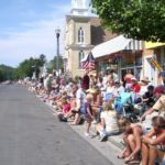 fourth of july in pentwater michigan. people sit on curb awaiting the parade. photo by bf newhall