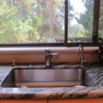 A large stainless steel kitchen sink with a woodsy view out the window. Photo by BF Newhall
