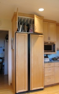 A cupboard over a refrigerator with vertical slats for storing platters, trays and cookie sheets. Photo by BF Newhall