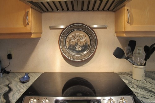 A stainless steel bar mounted over a ceramic cooktop holds a Tonala platter. Photo by BF Newhall