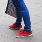 A Shanghai woman wears bright red canvas sneakers and tight blue slacks with blue and red tote bag. Photo by BF Newhall