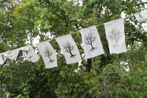 White prayer flags silk screened with images of dead trees hang in front of living green trees in Austin, TX. Photo by BF Newhall