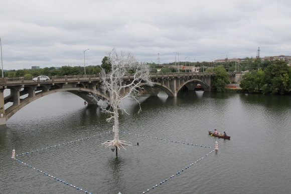 The temporary art installation THIST's Ghost Tree hovers above Lady Bird Lake, as seen from Austin, TX, Pfluger Pedestrian Bridge. Photo by BF Newhall