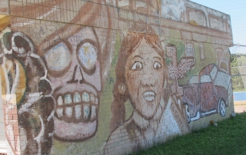 A light-coiored graffiti mural on a building in Austin TX with skull and a woman's face. Photo by BF Newhall