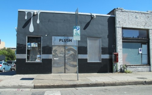 The Plush Dance Club in Austin TX has a sleek black and metallic storefront with silver drips painted over a windown. Photo by BF Newhall